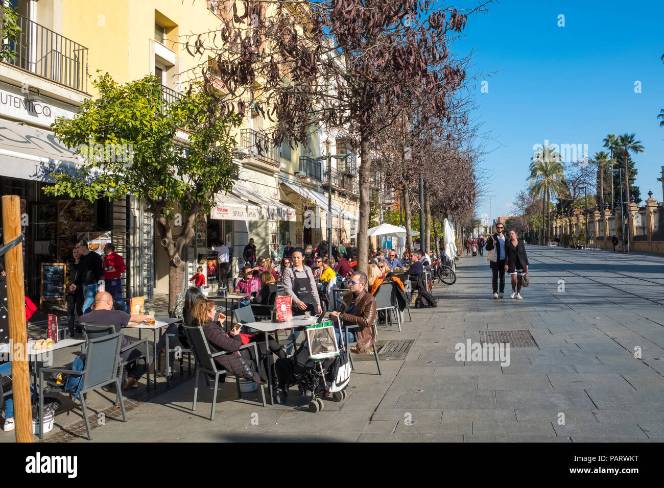 Seville pavement cafes with people sitting in the centre of Seville, Spain - Stock Image