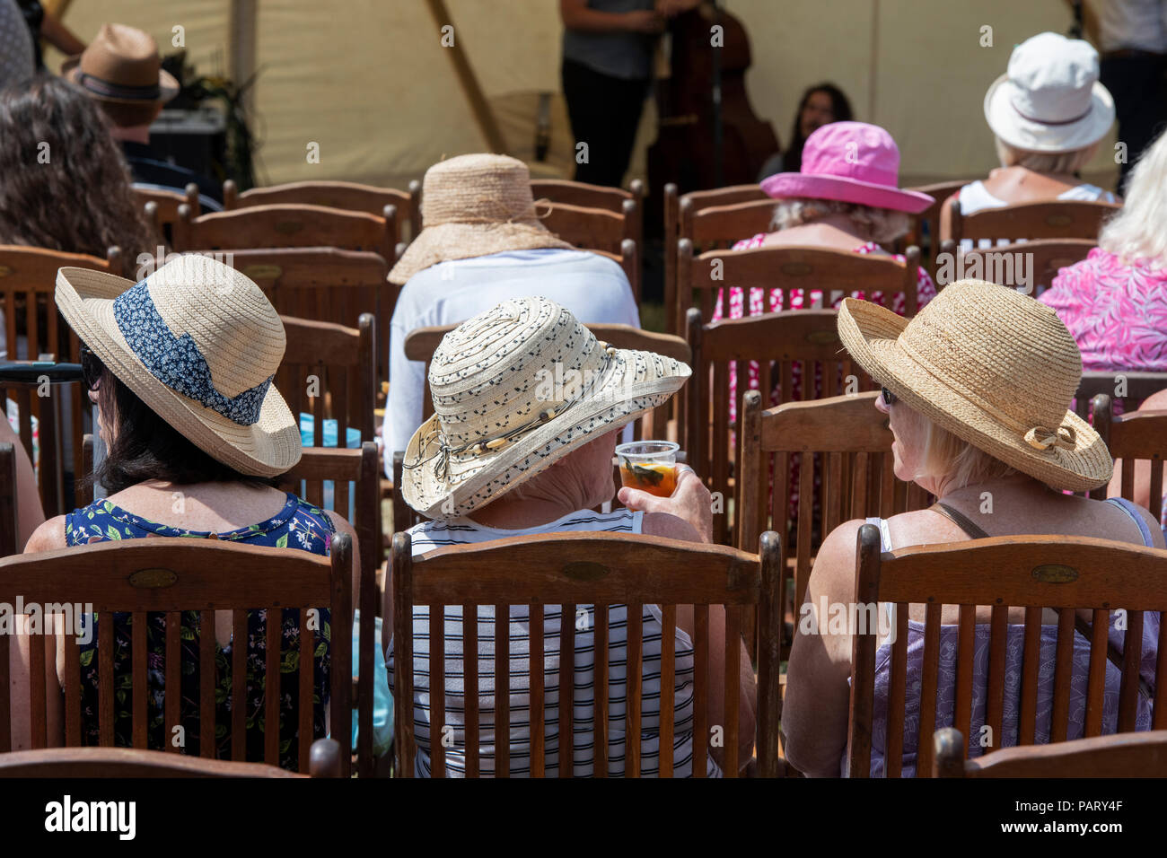 Women wearing summer hats sitting in wooden chairs at RHS Hampton court Flower show. London, UK - Stock Image