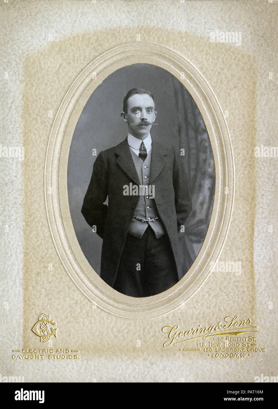 A portrait of a young Victorian or Edwardian man in an old photography studio. - Stock Image