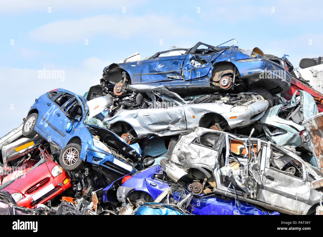 Cars at scrap metal business in recycling scrapyard smashed motor insurance written off car wreck in big heap awaiting crushing London England UK - Stock Image
