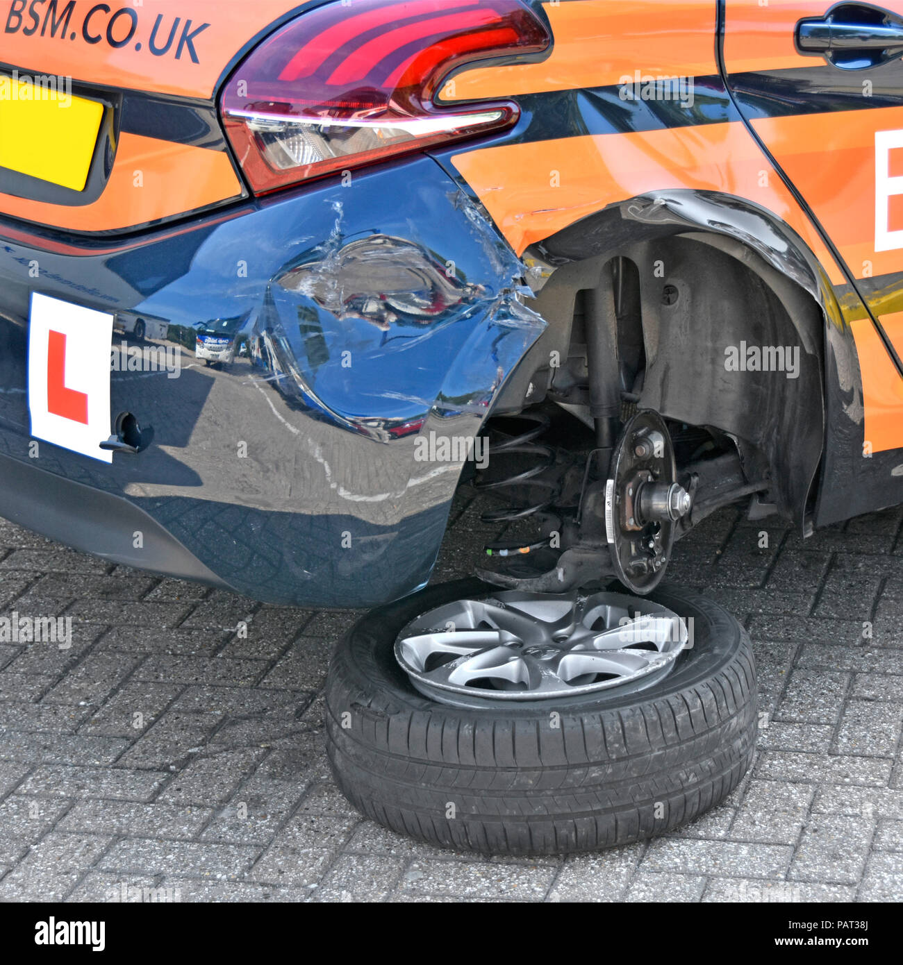 Rear wheel & tyre from L Plate hatchback car after car crash accident damaged BSM learner driver driving school car parked in service area England UK - Stock Image