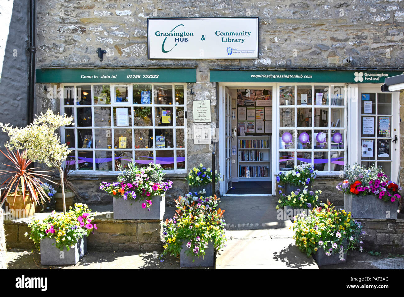 Grassington Hub Community Library project service run by mainly volunteer help shop front window & flower display Wharfedale North Yorkshire Dales UK - Stock Image