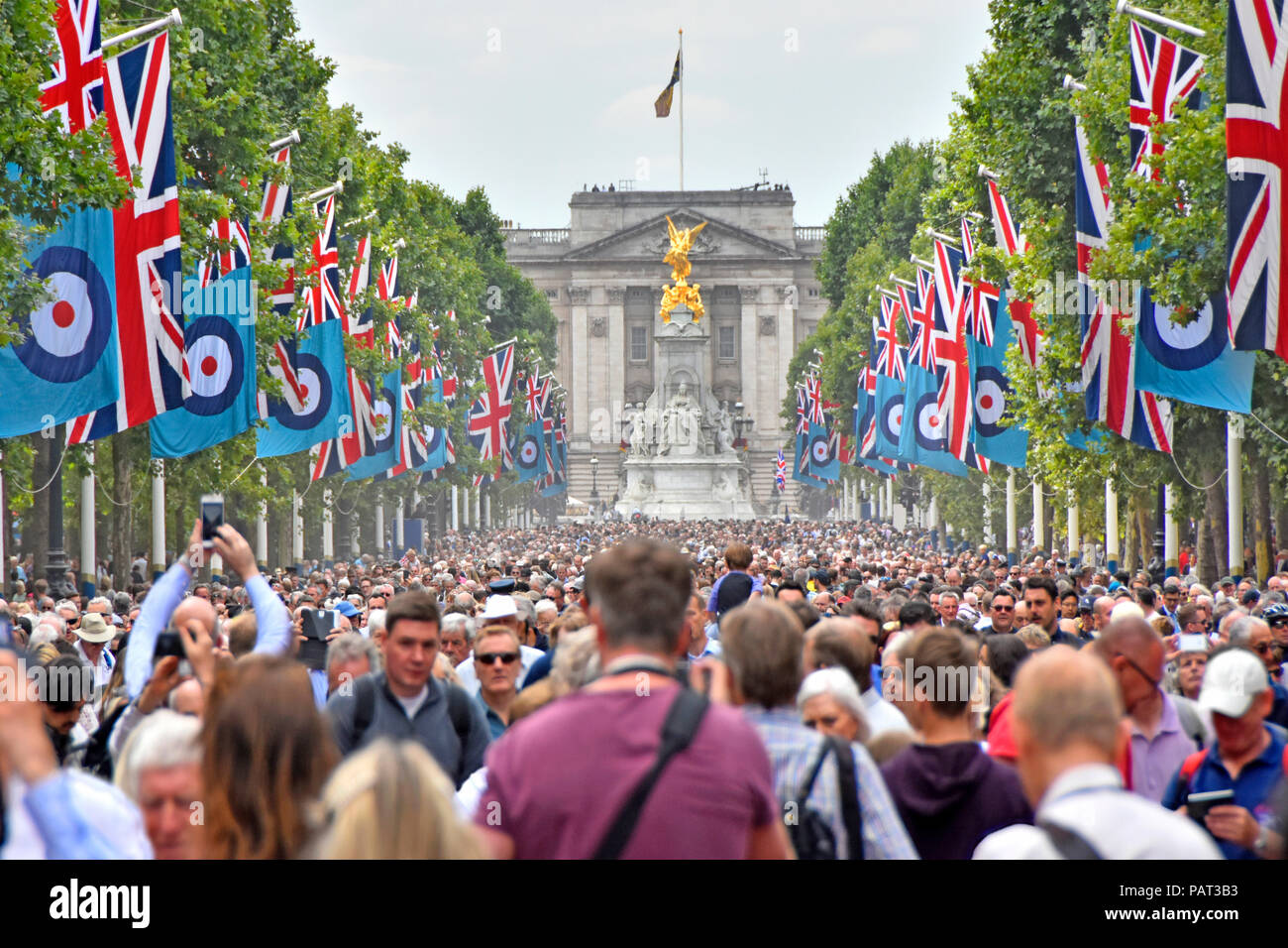 Street scene crowds of people in The Mall London at Royal Air force RAF centenary parade & flypast event Union Jack flags Buckingham Palace England UK - Stock Image