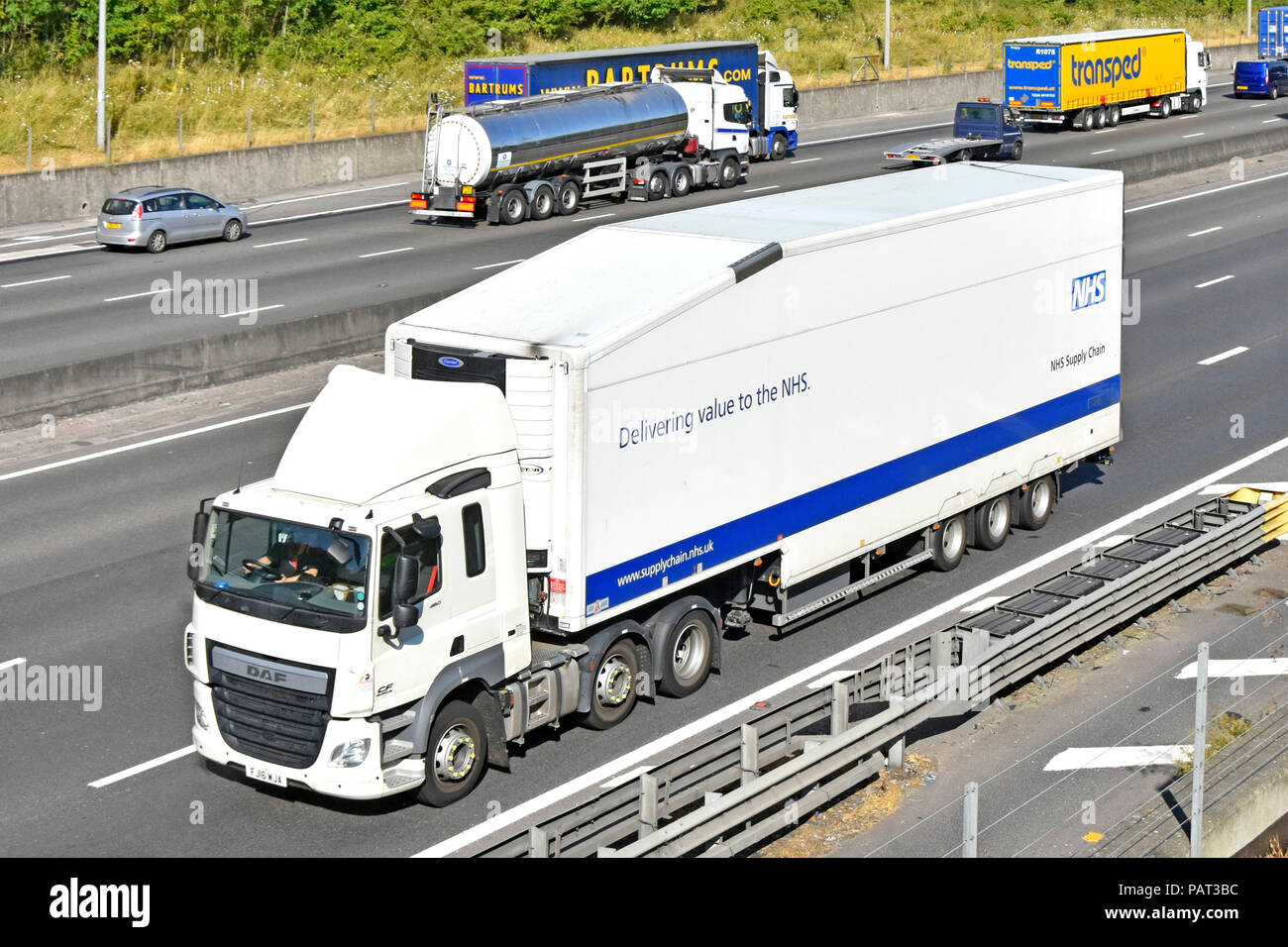 Side & front view of National Health Service healthcare supply chain DAF hgv NHS lorry truck & articulated trailer  driving along motorway England UK - Stock Image