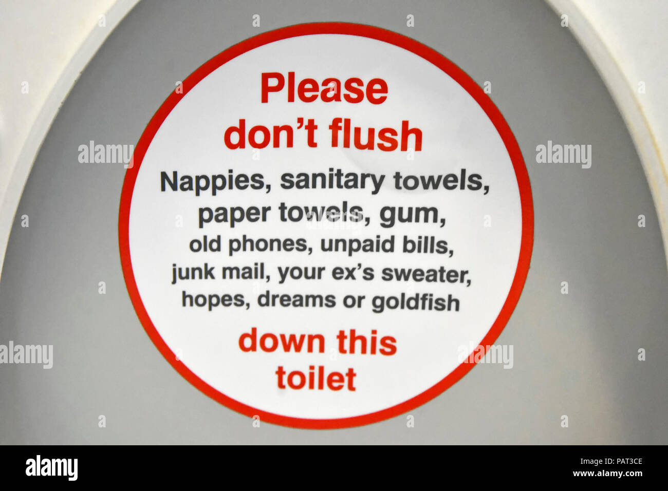Public transport humour onboard passenger train toilet seat lid humourous instructions items not to flush down loo lavatory pan WC London England UK - Stock Image