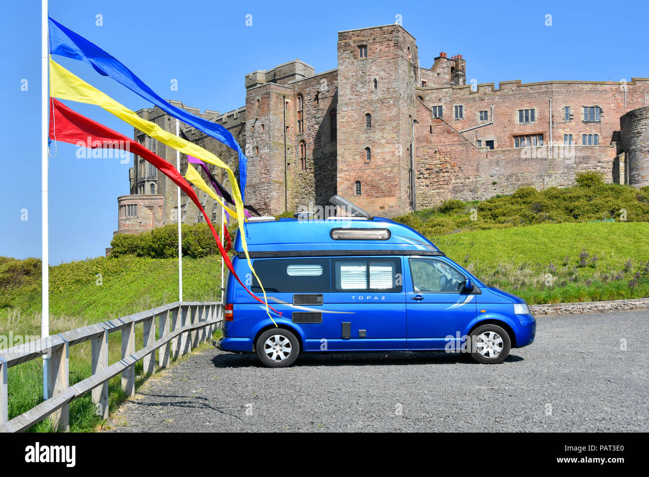 VW camper van tourist visitor car park colourful pennant flags Bamburgh Northumberland historical Bamburgh Castle tourism & listed building England UK - Stock Image
