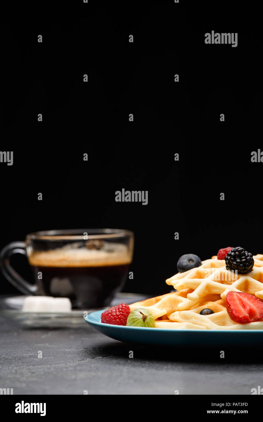 Photo of cup of coffee with sugar with Belgian waffles with strawberries, raspberries - Stock Image