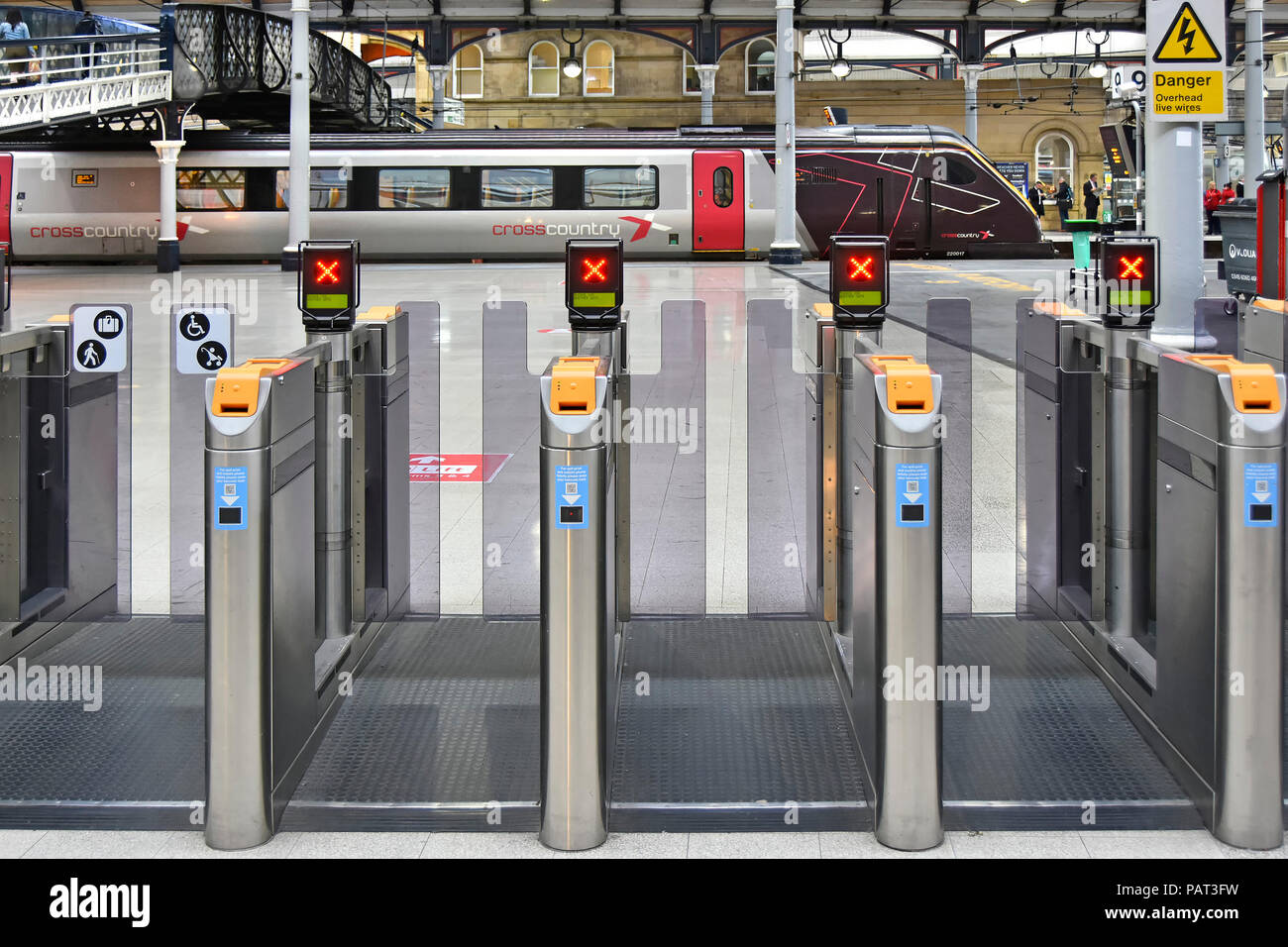 Rail ticket barrier no entry sign with Arriva Cross Country train at platform Newcastle upon Tyne public transport railway station Tyne and Wear UK - Stock Image