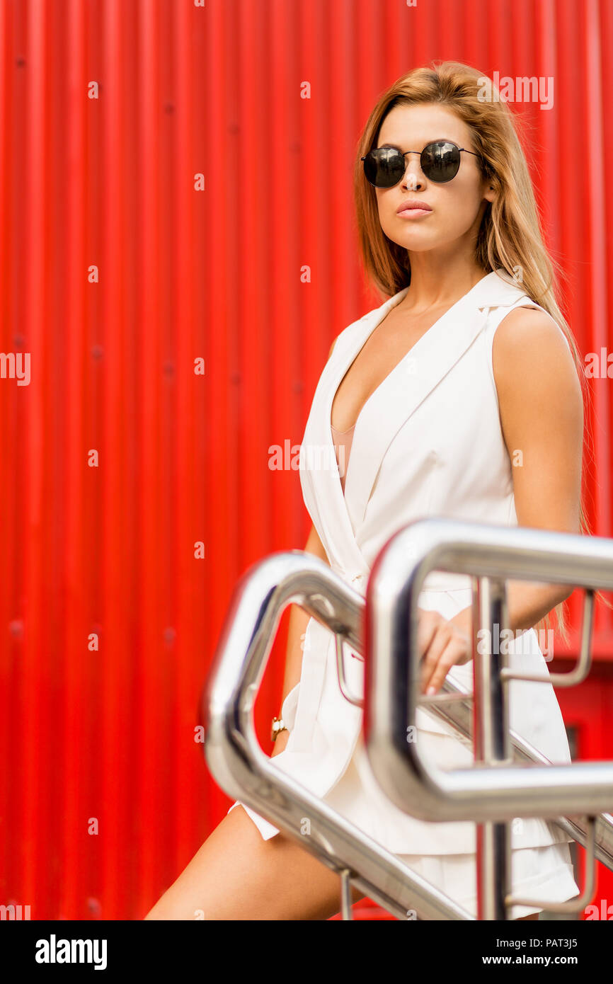 Fashion portrait of beautiful young business woman in white vogue suit walking up stairs against industrial red wall. Urban style girl, quick lifestyl - Stock Image