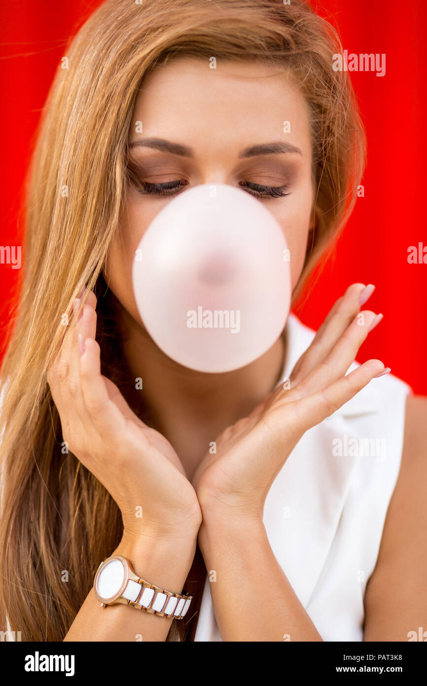 Funny portrait of beautiful young cute woman in white vogue suit look blowing gum bubble against industrial red wall. Urban style girl, quick lifestyl - Stock Image