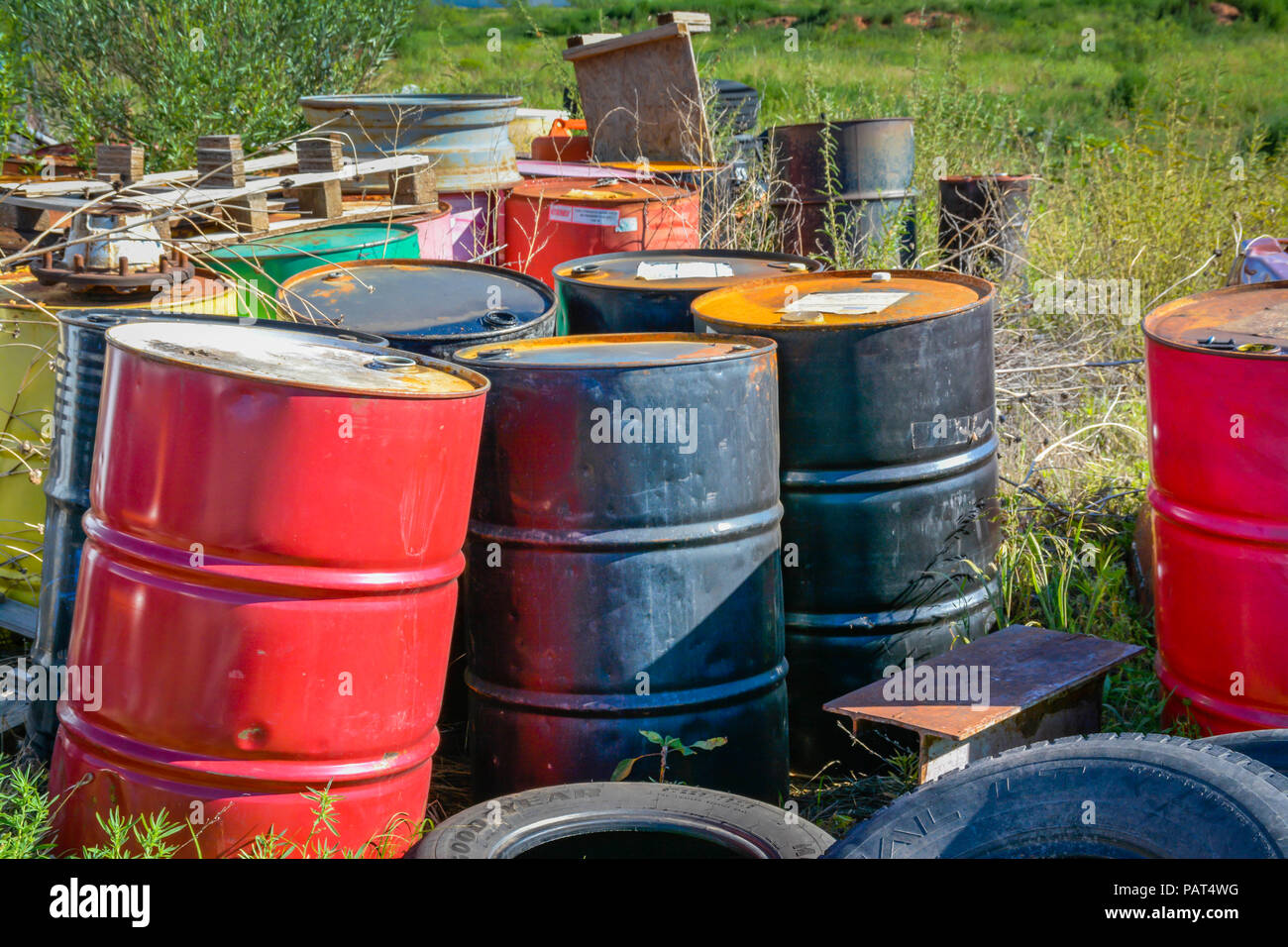 A colorful collection of dumped, old, oil drums in a field of old tires and rusty junk, creating a seemingly hazardous site - Stock Image