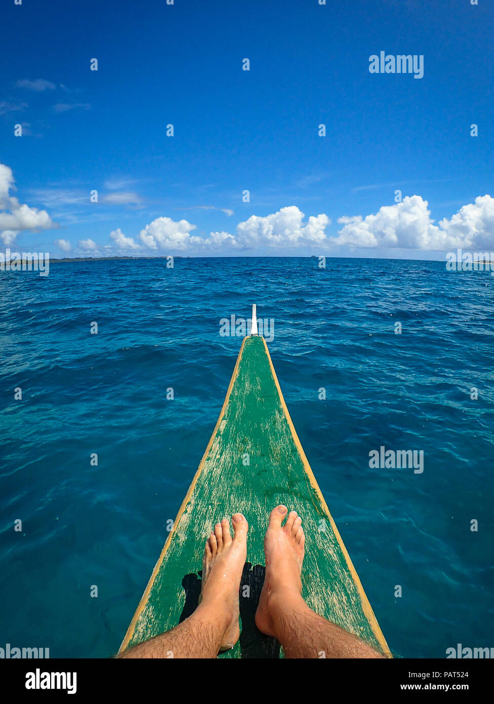 Tourist's bare feet on bow of wooden boat on the open sea, during island hopping tour - El Nido, Palawan - Philippines - Stock Image