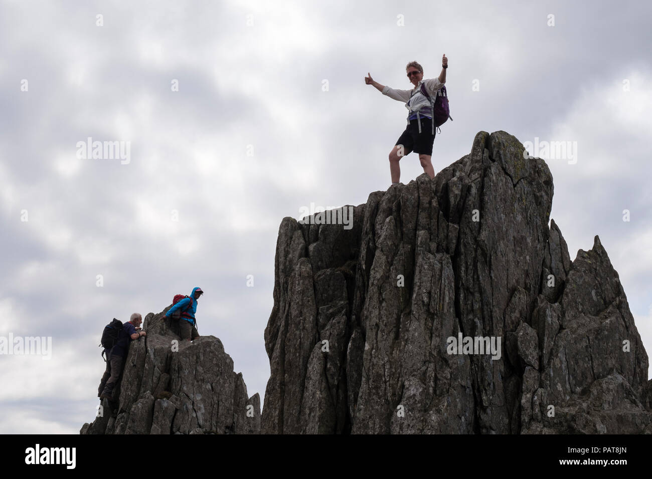 Female hiker feeling successful standing on a rock pinnacle on Glyder Fach in Snowdonia National Park. Ogwen, Conwy, Wales, UK, Britain - Stock Image