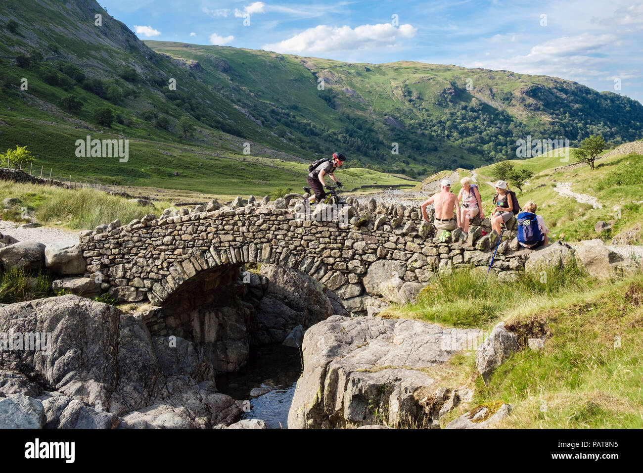 Mountain biker crossing Stockley Bridge with hikers resting on wall in Lake District National Park. Seathwaite Borrowdale Cumbria England UK Britain - Stock Image