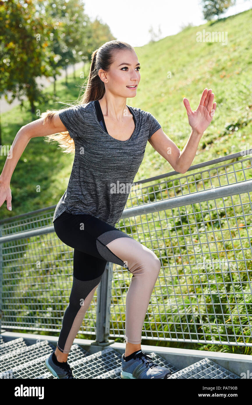 Young woman running on stairs in a park - Stock Image