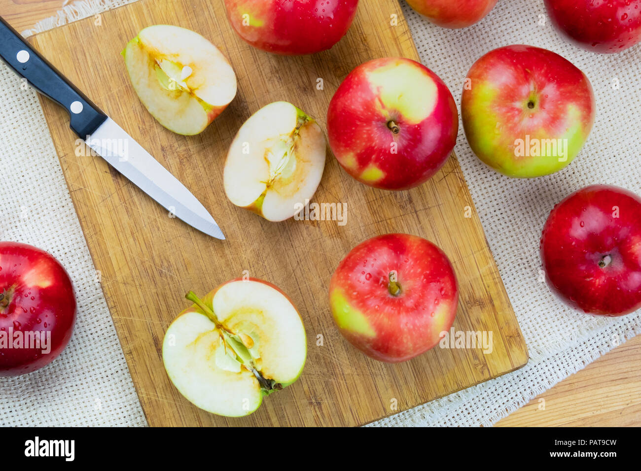 Top view of ripe juicy apples on rustic wooden table. Home grown organic apples and knife, shot from above - Stock Image