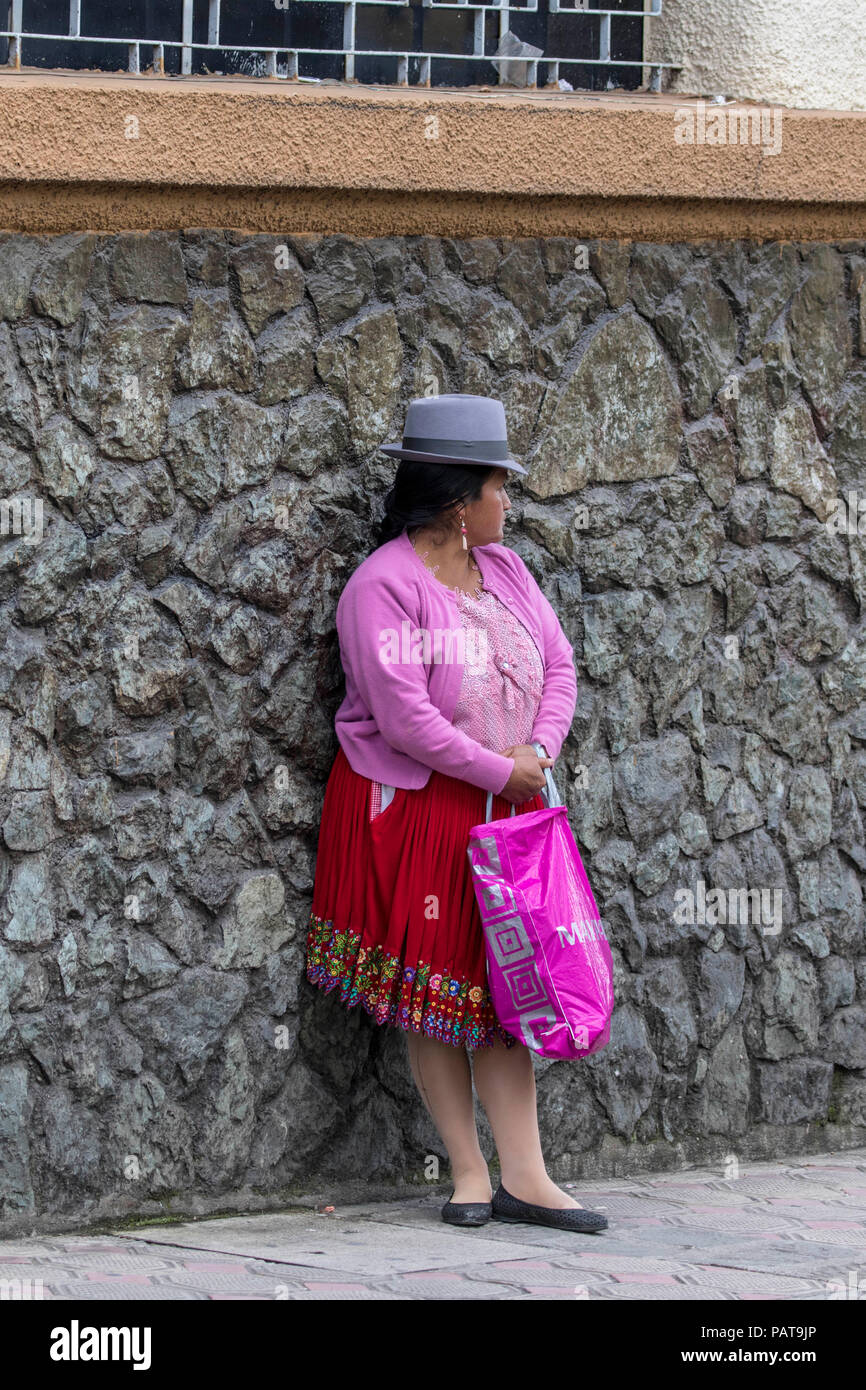 Native Latin woman in pink dress standing on the sidewalk in Ecuador - Stock Image