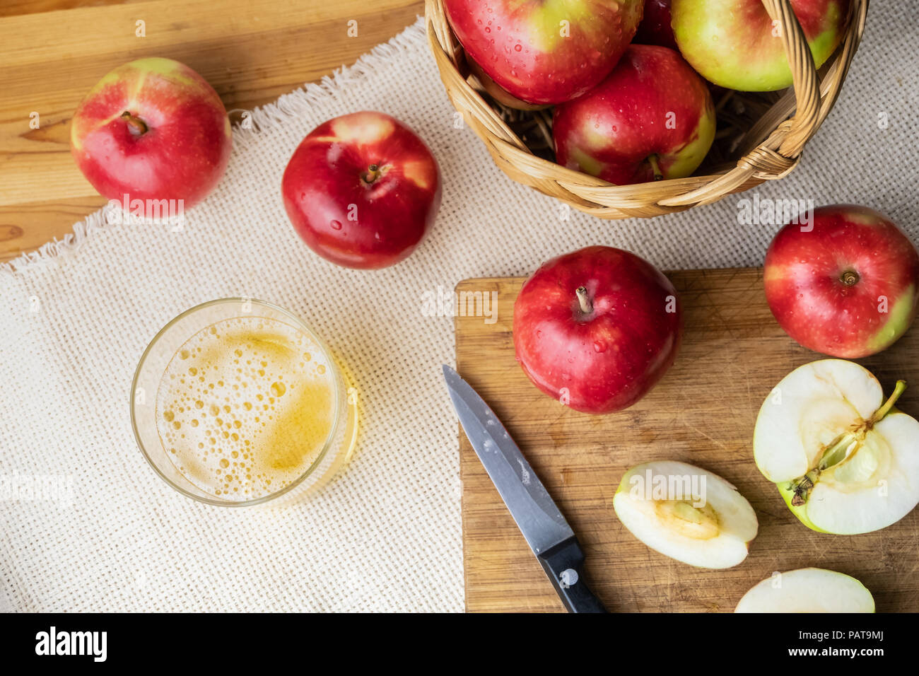 Top view of ripe juicy apples and glass of cidre drink on rustic wooden table. Glass of home made cider and locally grown organic apples, shot from ab - Stock Image