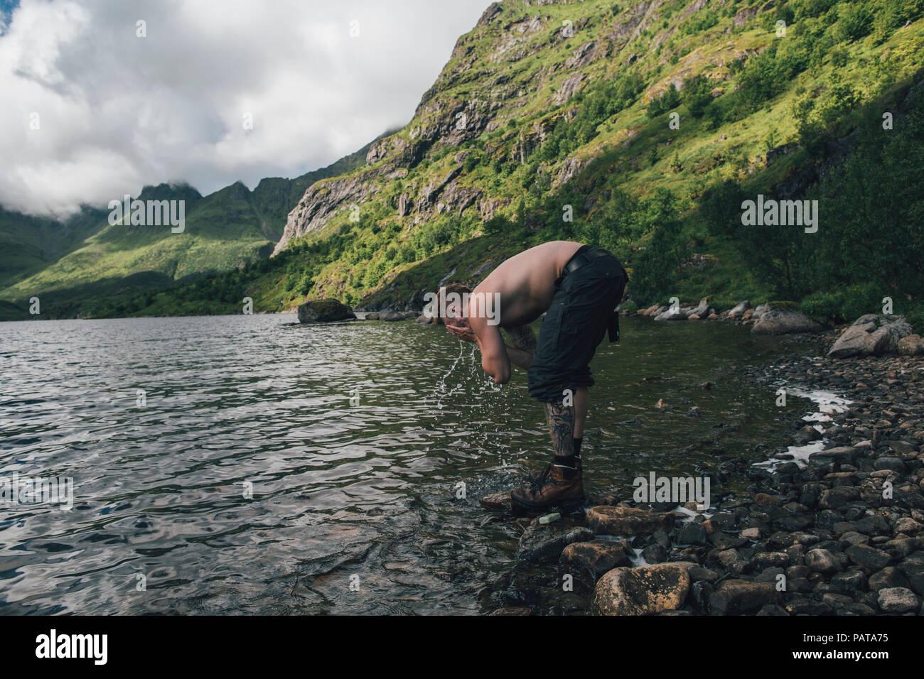 Norway, Lofoten, Moskenesoy, Young man washing his face in Agvatnet lake - Stock Image