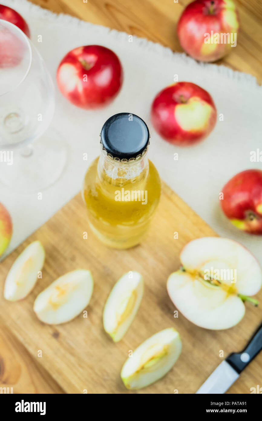 Top view cidre bottle on and ripe apples rustic wooden table. Glass and bottle of home made cider and locally grown organic apples, shot from above - Stock Image