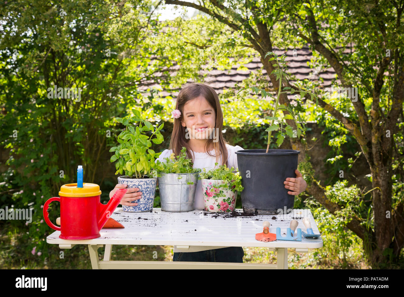 Portrait of proud little girl with potted spice plants on table in the garden - Stock Image