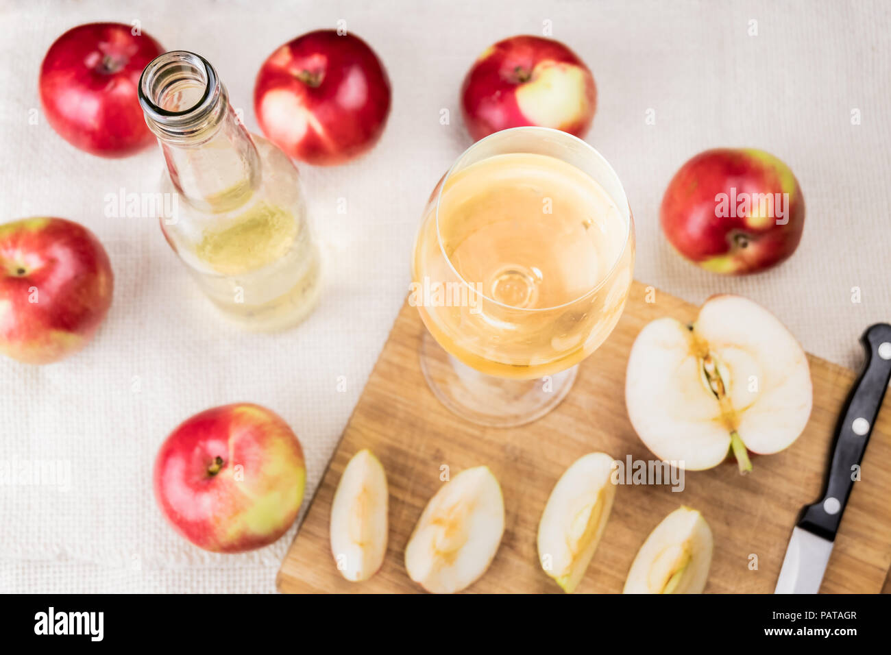 Flat lay with glass of cidre drink on rustic wooden table. Top view of home made cider and locally grown organic apples - Stock Image