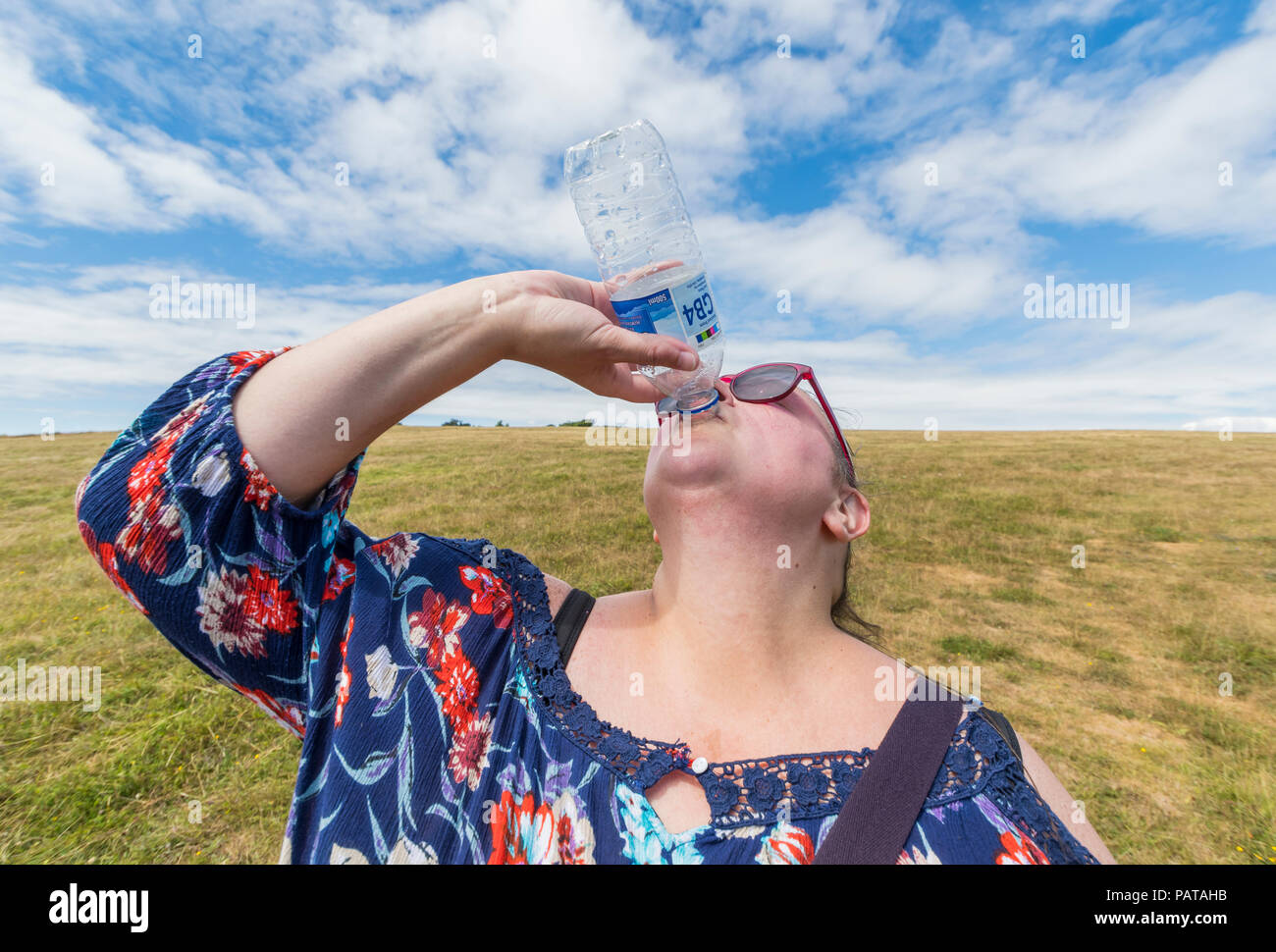 Woman drinking water from a bottle to stay hydrated on a very hot summer day during a heatwave in the UK in July 2018. Refreshed. - Stock Image