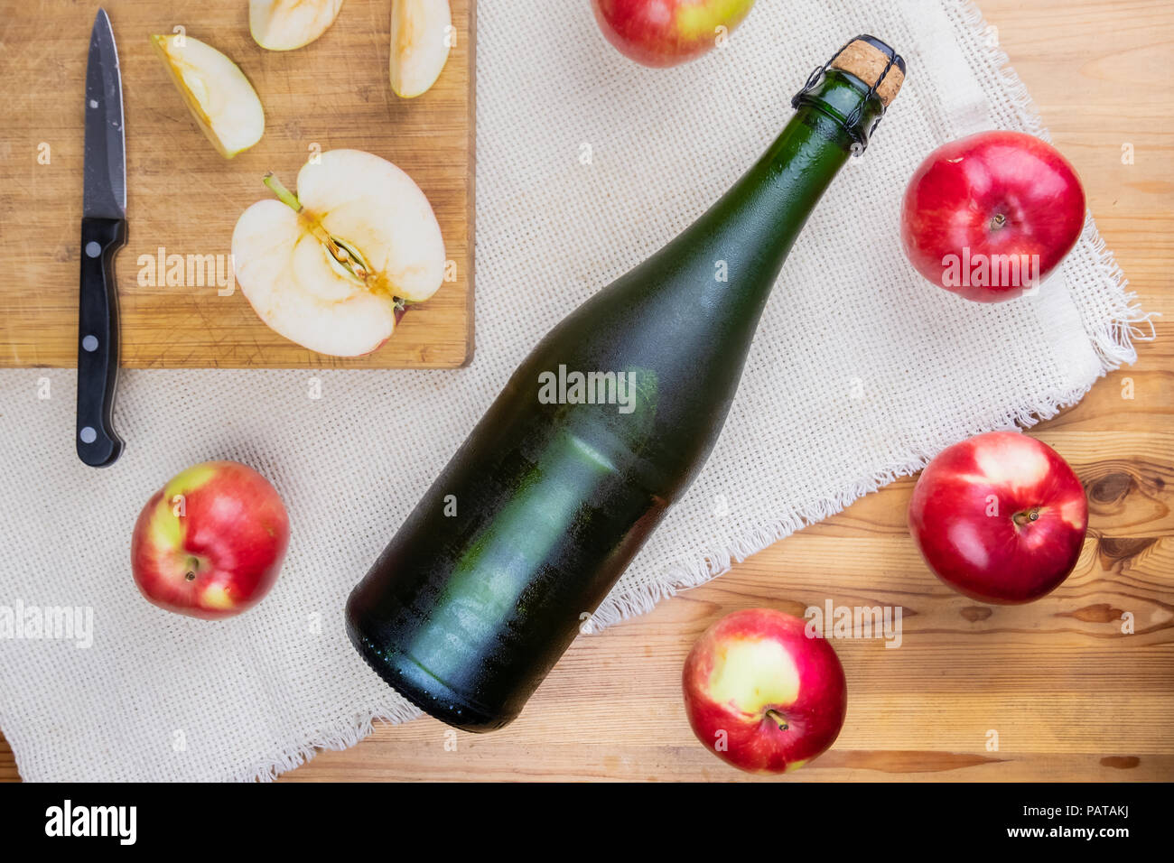 Flat lay with icy cooled corked cidre bottle on rustic wooden table. Top view of premium cider and locally grown organic apples - Stock Image