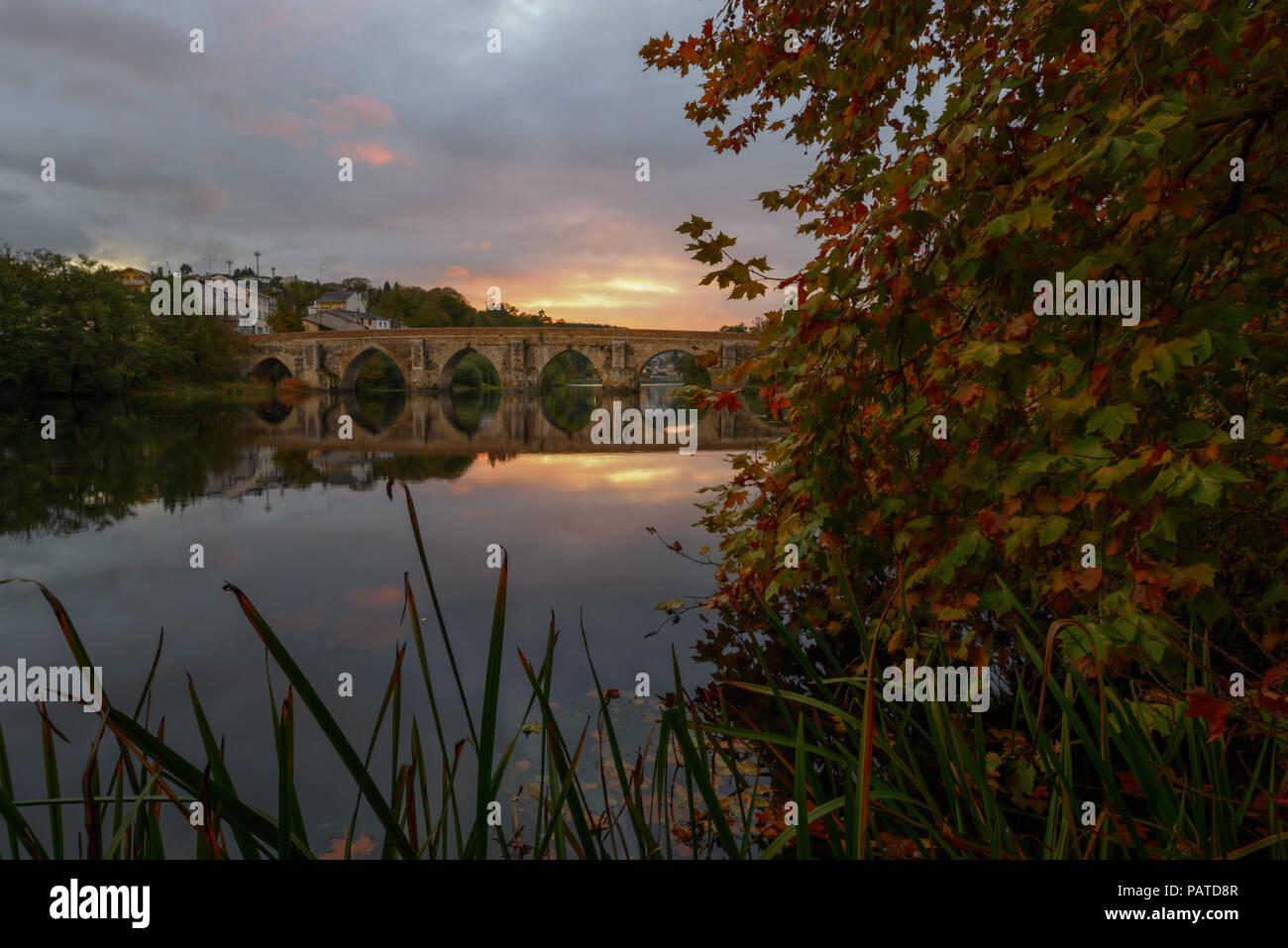 El puente romano sobre el río Miño al atardecer, en Lugo, Galicia - Stock Image
