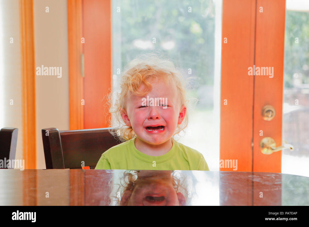 Crying Child at Kitchen counter with background area Stock Photo