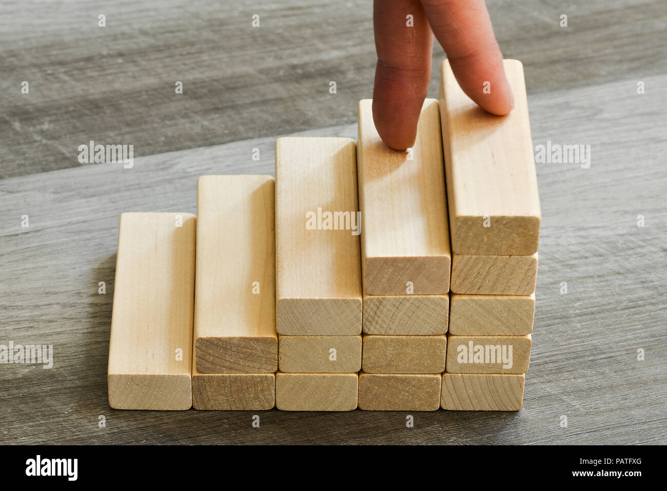 Fingers Climbing Up To Top Of Stairway Over Dark Wooden Background - Success Concept - Stock Image