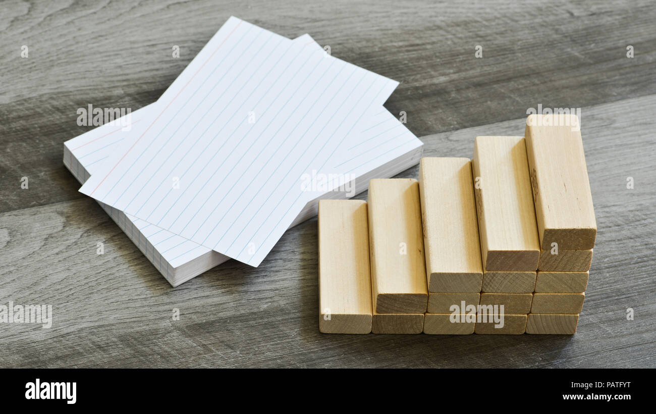 Business / Education Challenge Concept - Blank Index Cards With Stairway Upwards Of Building Blocks Over Dark Grey Wooden Background - Stock Image