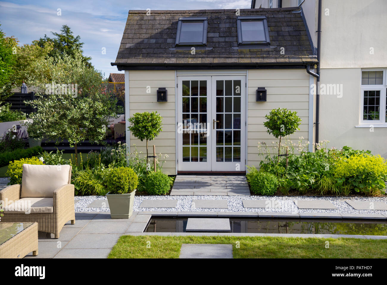View of house exterior with herbaceous borders, Viburnum tinus topiary and London Stone granite paving - Stock Image