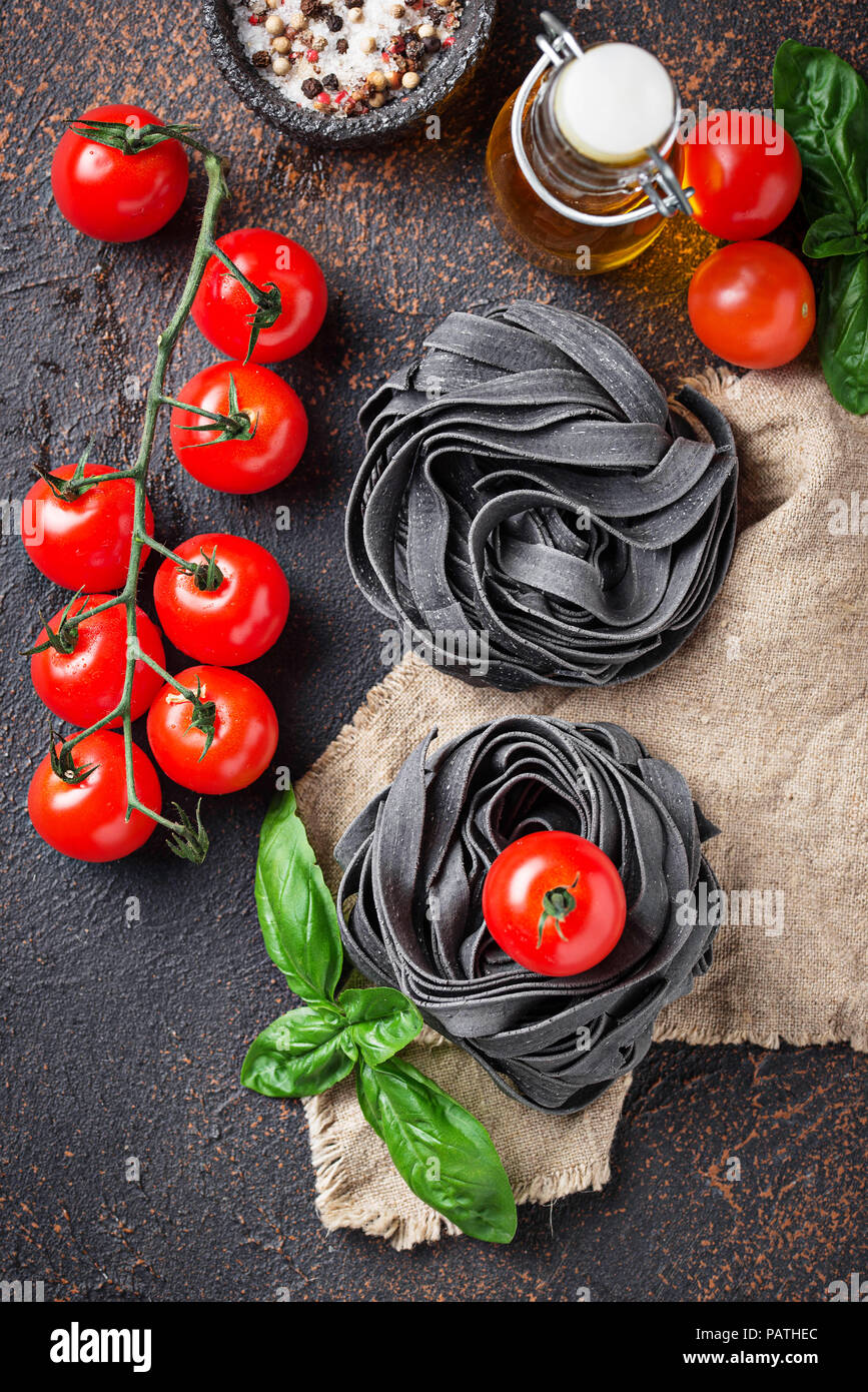 Black uncooked pasta  with tomato and basil - Stock Image