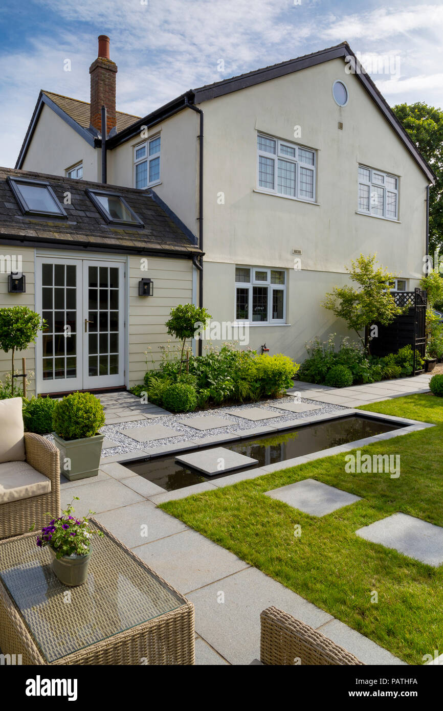 Overview of herbaceous borders surrounding house exterior, London Stone granite paving and a pool water feature - Stock Image