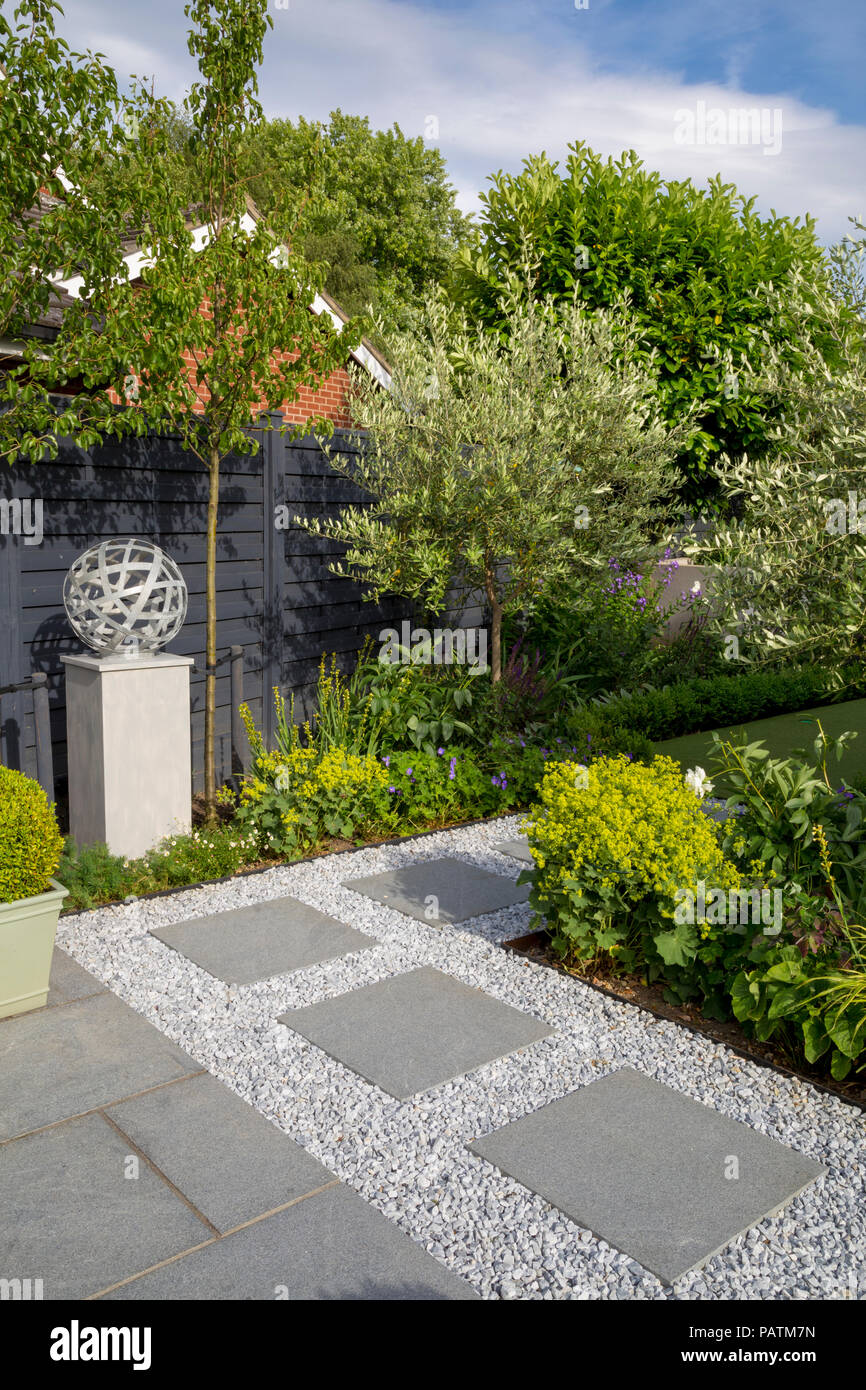 London Stone granite paving leading past herbaceous borders to the golf putting lawn - Stock Image