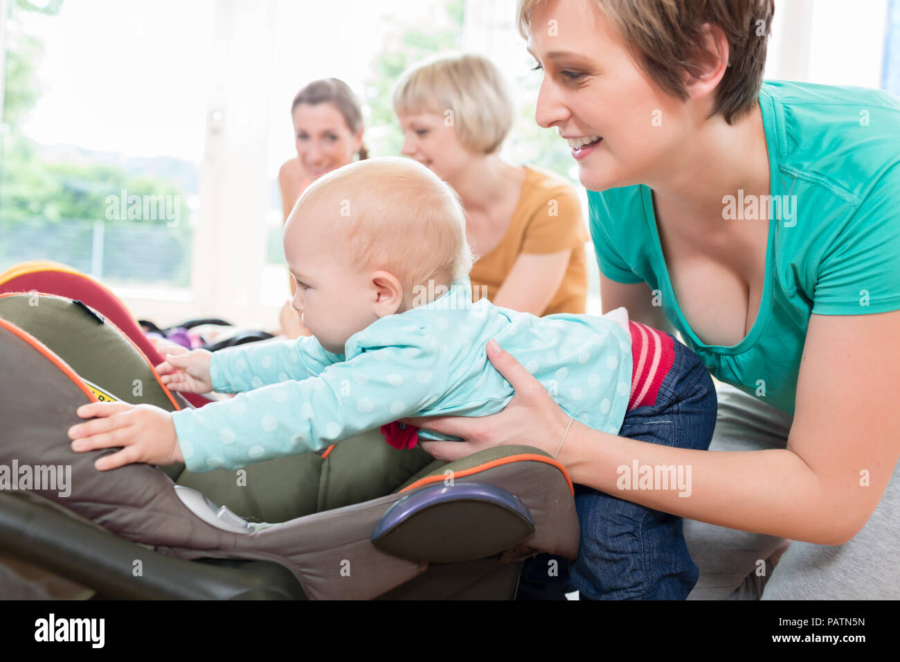 Moms and babies in mother and child course practicing - Stock Image