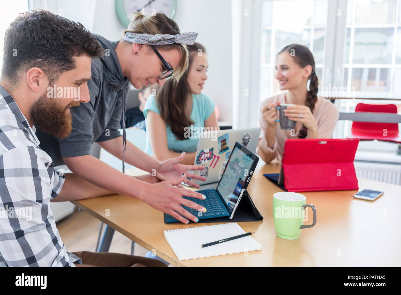 man and woman cooperating as co-workers in collaborative office  - Stock Image