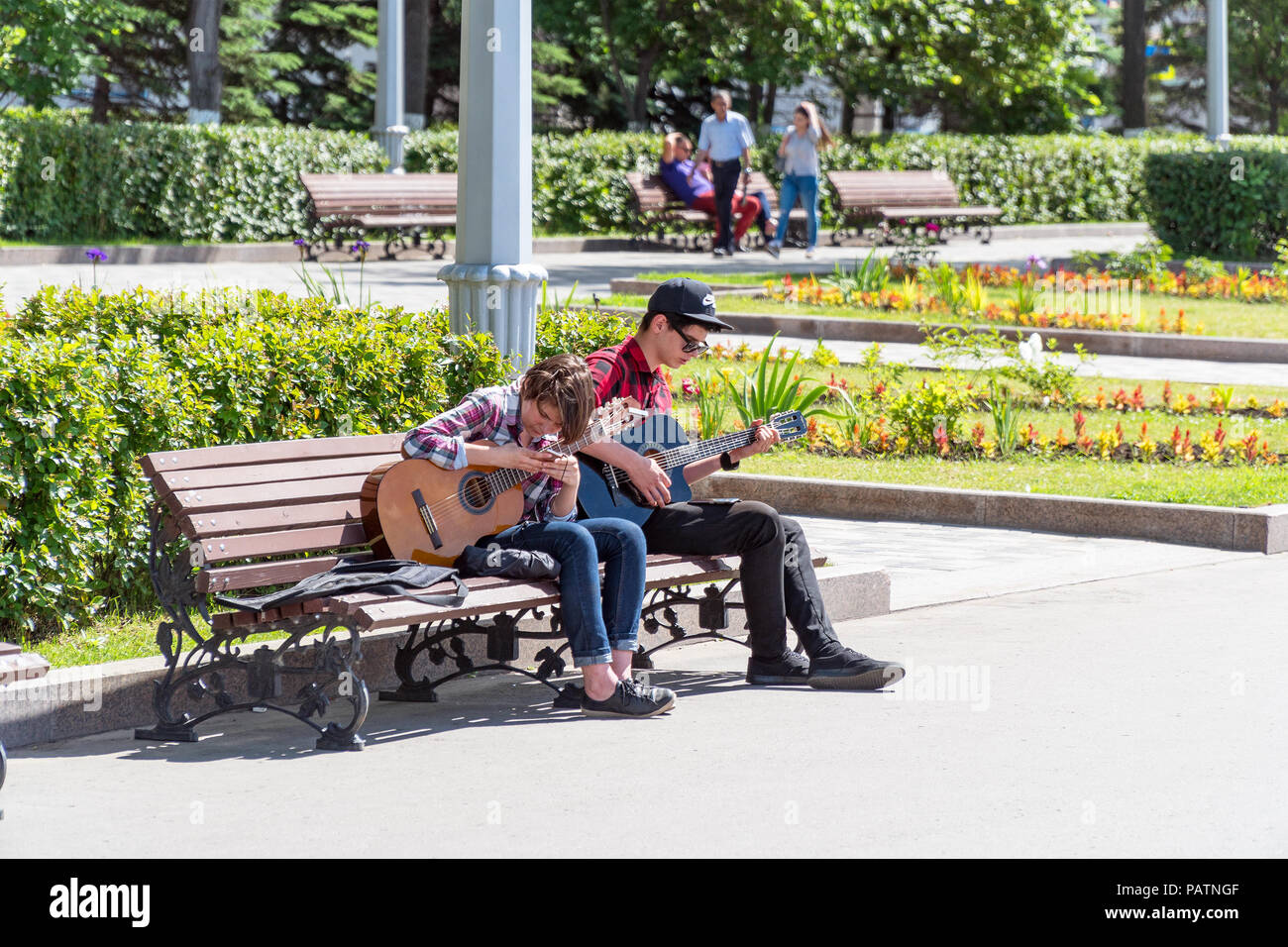 Two young street musicians with guitars on a Park bench - Stock Image