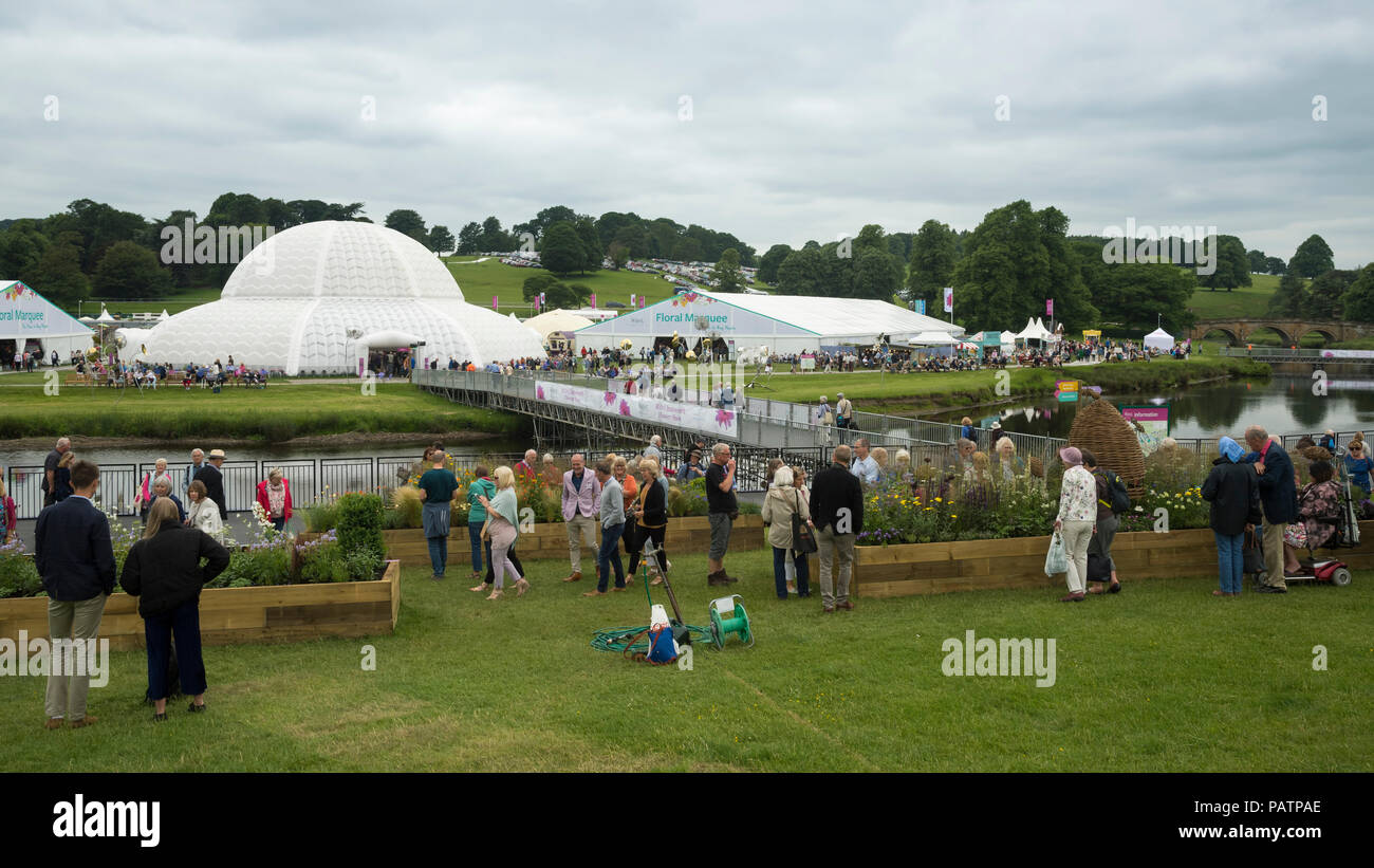 Showground at RHS Chatsworth Flower Show (people by exhibits, marquee, Great Conservatory dome, river & temporary bridge) Derbyshire, England, UK. - Stock Image
