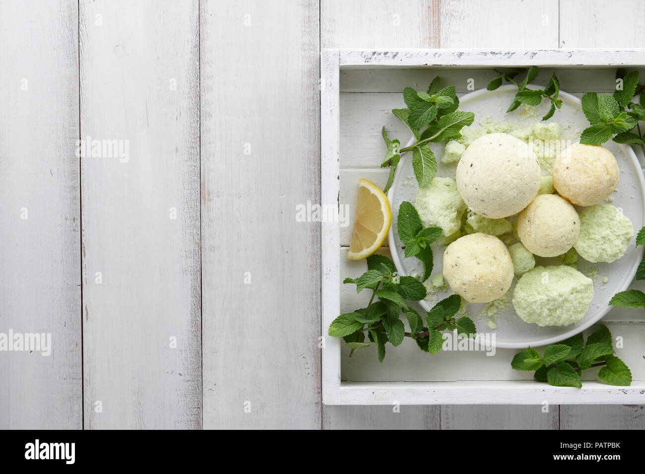 Handmade mint bath bombs with fresh herbs in white tray - Stock Image