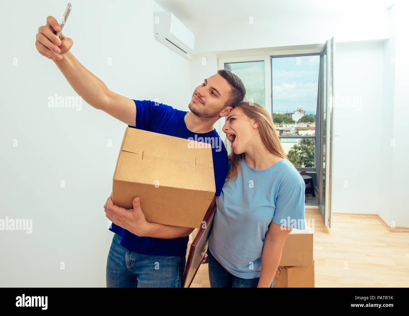48ddf6ef2064 Handsome man make selfie with cell phone while holding cardboard box in new  home image jpg