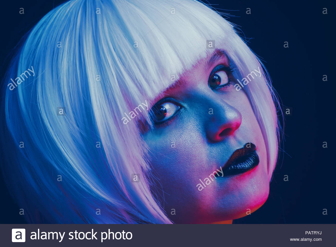 Artistic portrait of a young woman illuminated by color lights - Stock Image