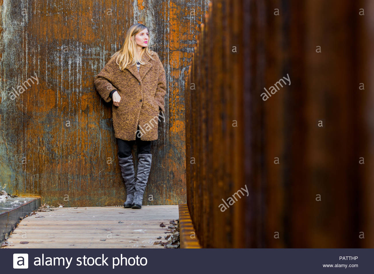 Woman in warm clothing standing against a wall - Stock Image