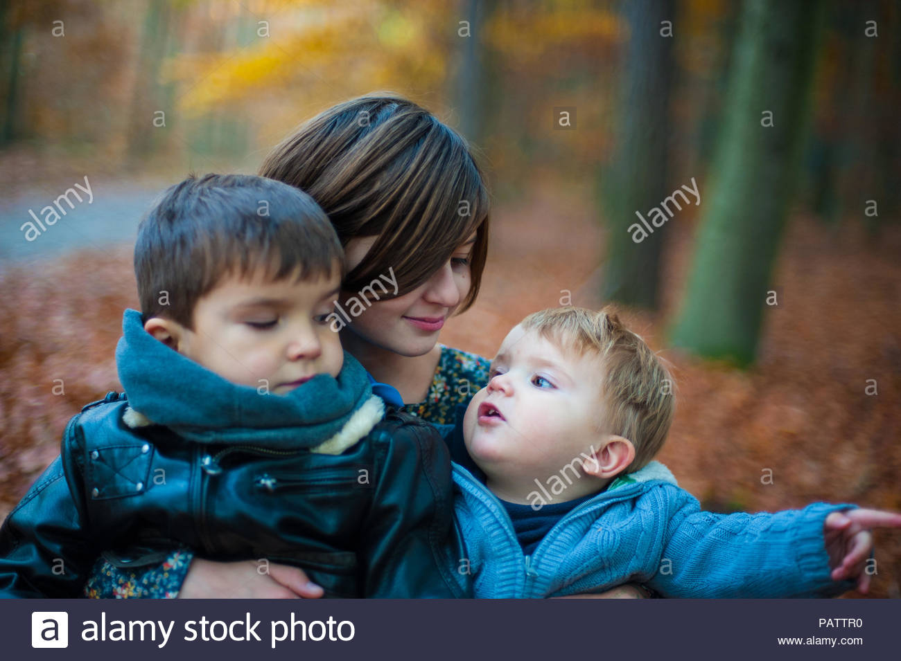 Close-up shot of a mother with her two sons outdoors together - Stock Image