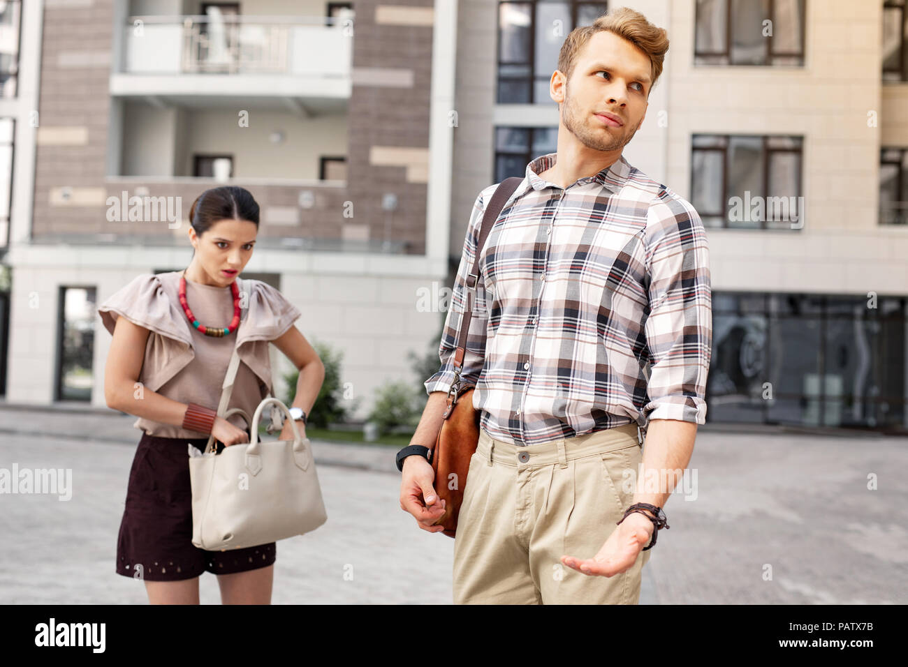 Unhappy irritated man waiting for his wife - Stock Image