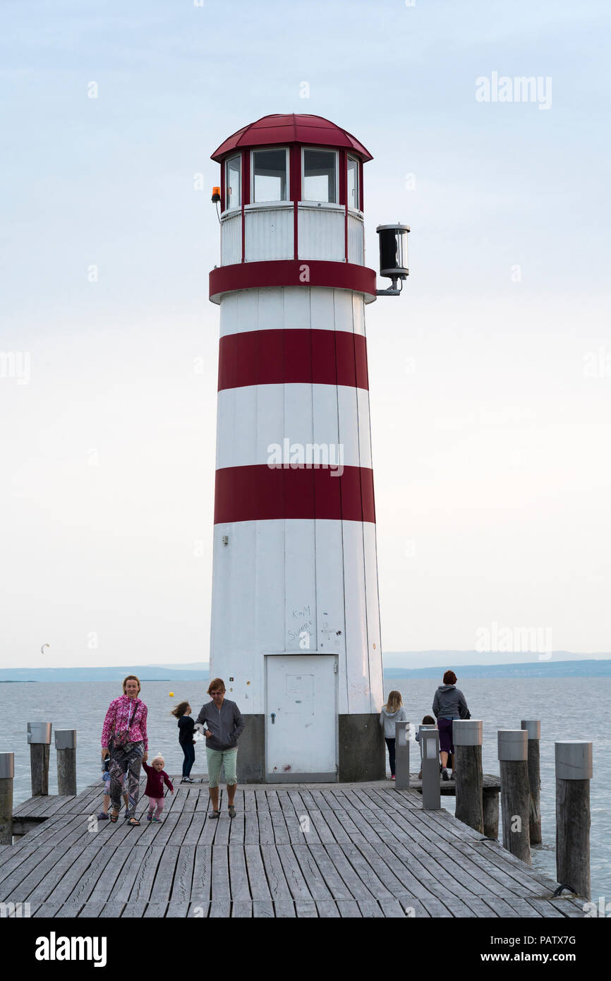 Tourists at the Podersdorf Lighthouse at sunset in summer on the shore of the Neusiedler See, Burgenland, Austria - Stock Image