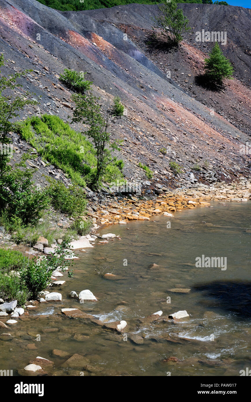 Coal mine tailings waste spoil pile beside a stream with orange rocks showing environmental damage from toxic pollution and acid mine drainage. - Stock Image