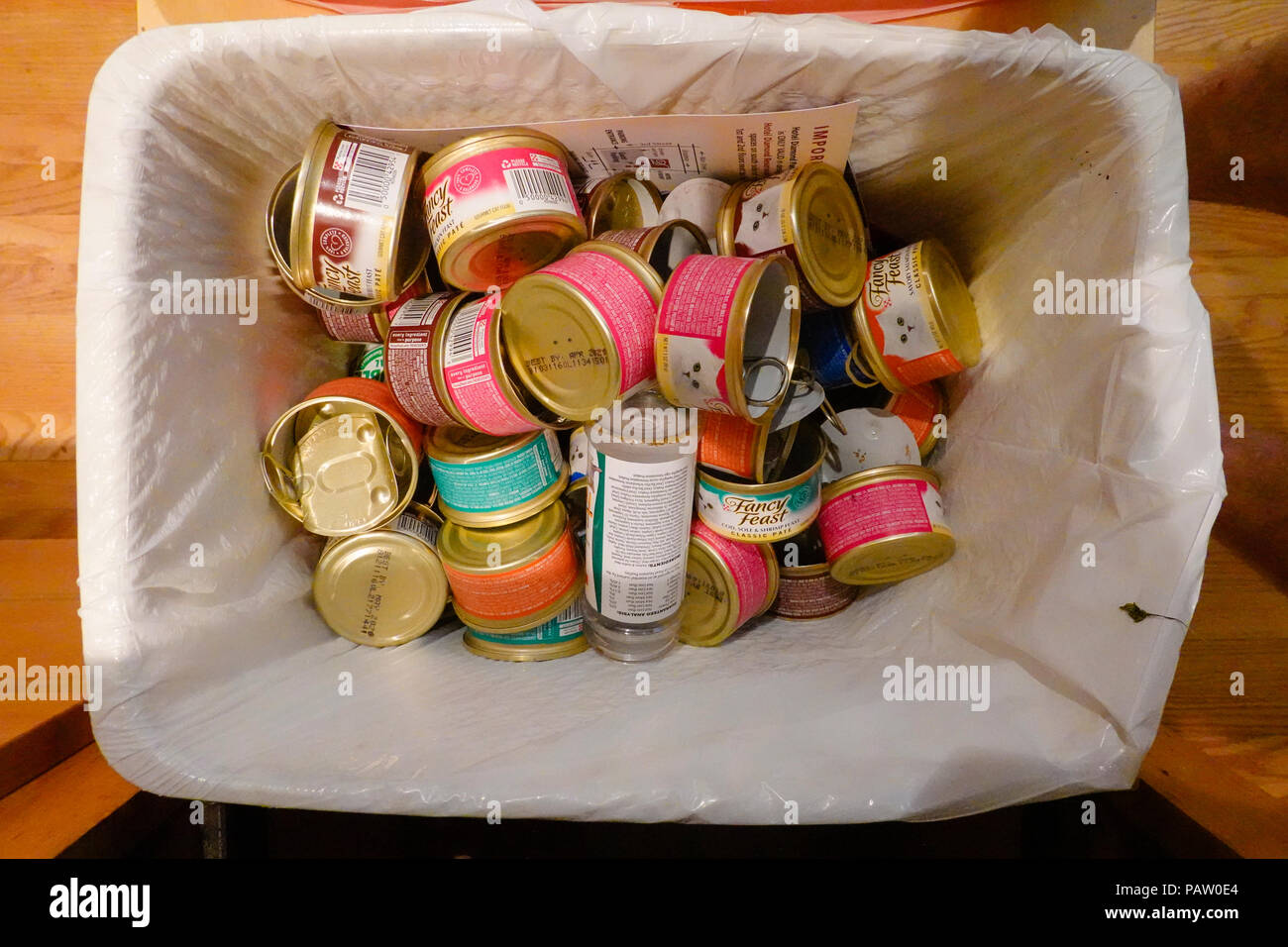 Empty cat food cans in a kitchen recycling bin. - Stock Image