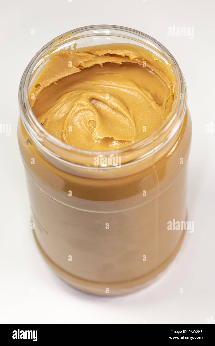A jar of organic peanut butter sitting on the kitchen table waiting to be eaten - Stock Image